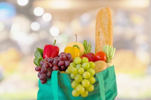 Frutta fresca e verdura in sacchetto della spesa verde riutilizzabile con drogheria del supermercato sfocato sfondo sfocato con luce bokeh