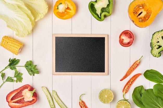 Bordo vintage di frutta e verdura fresca e piatto di ardesia per il tuo testo