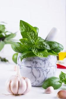 Erbe fresche del basilico del giardino in mortaio e olio d'oliva, aglio, peperoncini roventi, limone sui precedenti bianchi.