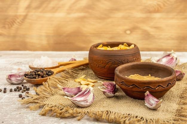 Aglio fresco e suoi prodotti: pezzi secchi e polvere. ingredienti naturali per cucinare cibi sani. sfondo in legno chiaro, copia spazio