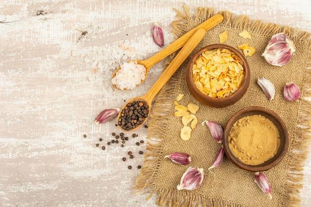 Aglio fresco e suoi prodotti: pezzi secchi e polvere. ingredienti naturali per cucinare cibi sani. fondo in legno chiaro, vista dall'alto