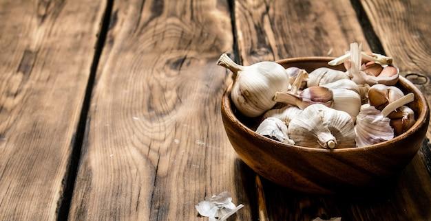 L'aglio fresco in una ciotola di legno. sullo sfondo di legno.