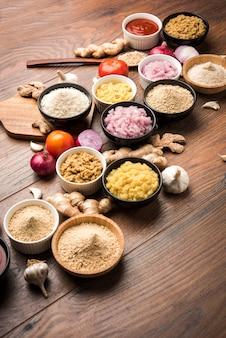 Zenzero fresco, aglio, cipolla e purea di pomodoro conosciuta anche come pasta di adrak, lahsun, pyaj e tamatar in hindi. ingredienti alimentari indiani di base in una ciotola su sfondo lunatico