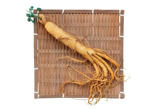 Radice di ginseng fresca sul cesto di bambù con foglie verdi e bacche