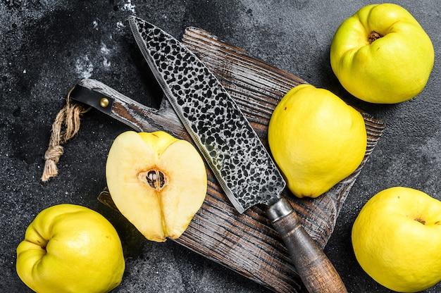 Frutta mela cotogna oro fresco su un tagliere. sfondo nero. vista dall'alto.
