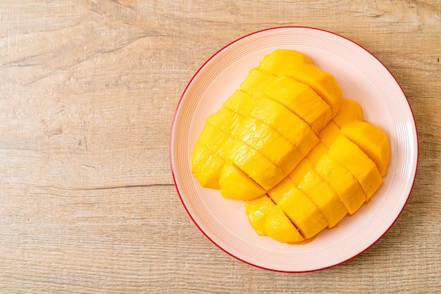 Mango fresco e dorato affettato sul piatto