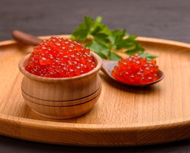 Caviale di salmone chum rosso granuloso fresco in una ciotola di legno, cibo delizioso e sano, primi piani