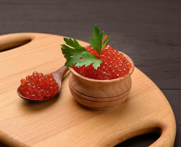 Caviale di salmone chum rosso granuloso fresco in un piatto di legno, cibo delizioso e sano, primi piani