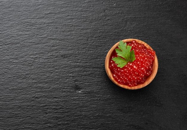 Caviale di salmone chum rosso granuloso fresco in un piatto di legno, cibo delizioso e sano, vista dall'alto