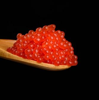 Caviale di salmone chum rosso granuloso fresco in un cucchiaio di legno, cibo delizioso e sano, primi piani
