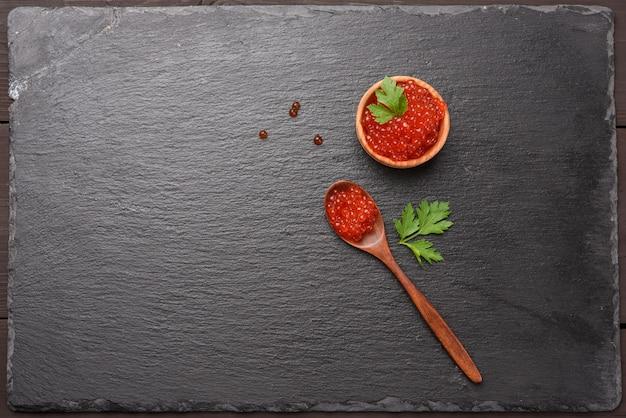 Caviale di salmone chum rosso granuloso fresco in un cucchiaio di legno, cibo delizioso e sano, vista dall'alto