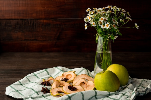 Mele fresche di granny smith, vaso con fiori da giardino, frutta secca e anice stellato su asciugatutto a scacchi su tavola di legno scuro contro la parete