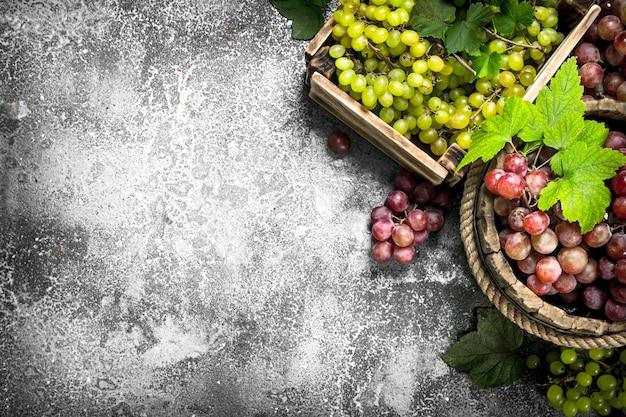 Uva fresca in un secchio di legno. su fondo rustico.