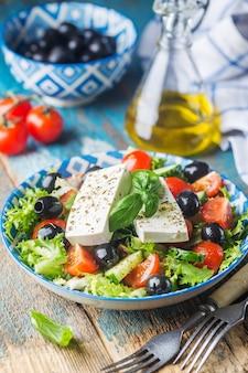 Insalata greca fresca di cetriolo, pomodoro, peperone dolce, cipolla rossa, formaggio feta e olive con olio d'oliva