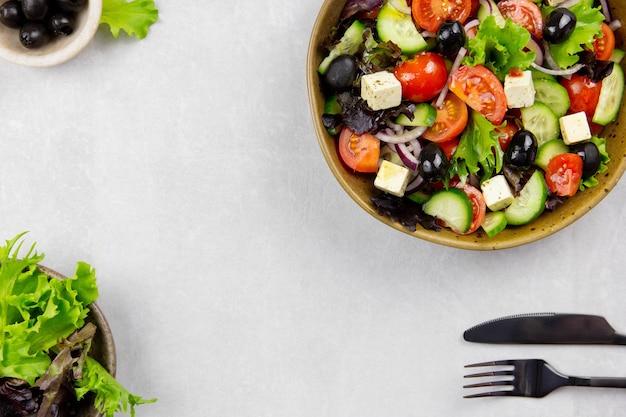 Insalata greca fresca con pomodorini, cetrioli, lattuga, olive nere, formaggio feta e olio di olive su superficie grigio chiaro