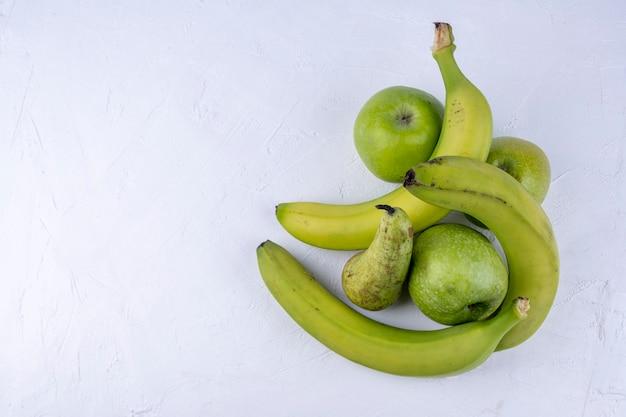 Mele verdi fresche, pere, banane su un fondo di legno bianco. foto di cibo sano di concetto.