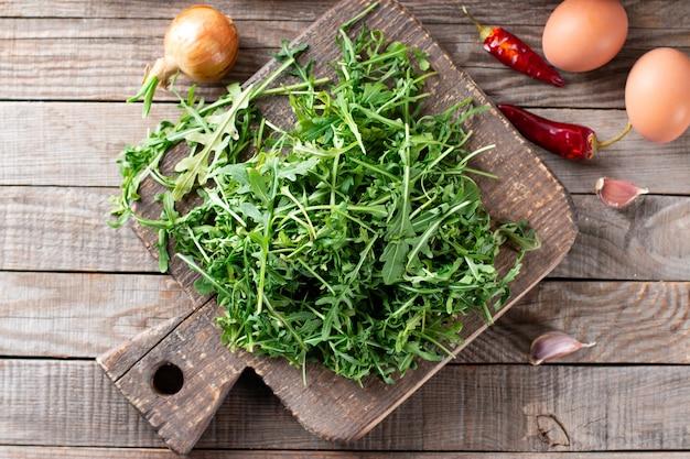 Rucola verde fresca su un tagliere sulla tavola di legno.