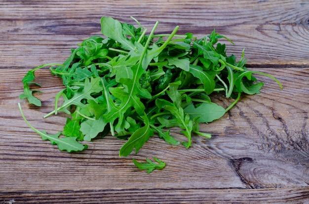 Rucola verde fresca sulla tavola di legno dalle vecchie tavole. foto di studio