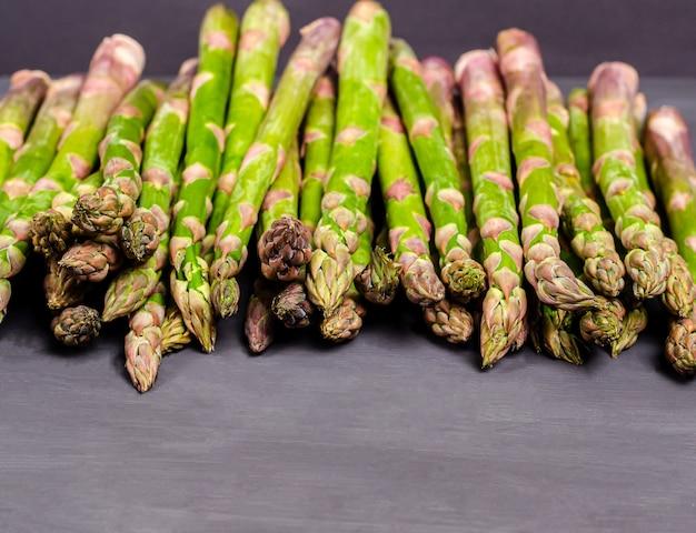 Asparagi verdi freschi su sfondo nero. raccolto stagionale primaverile. lay piatto, copia spazio. concetto di cibo sano. avvicinamento