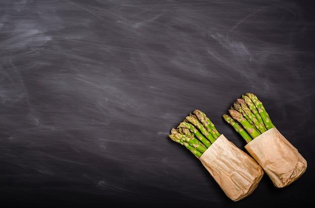 Asparagi verdi freschi su sfondo nero con posto per il testo. raccolto stagionale primaverile. lay piatto, copia spazio. concetto di cibo sano