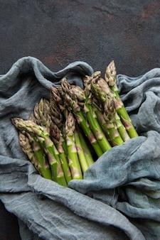 Asparagi verdi freschi su cemento nero. lay piatto