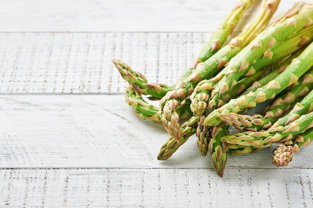 Mazzo di asparagi verdi freschi pronto per la cottura su vecchio fondo di legno bianco