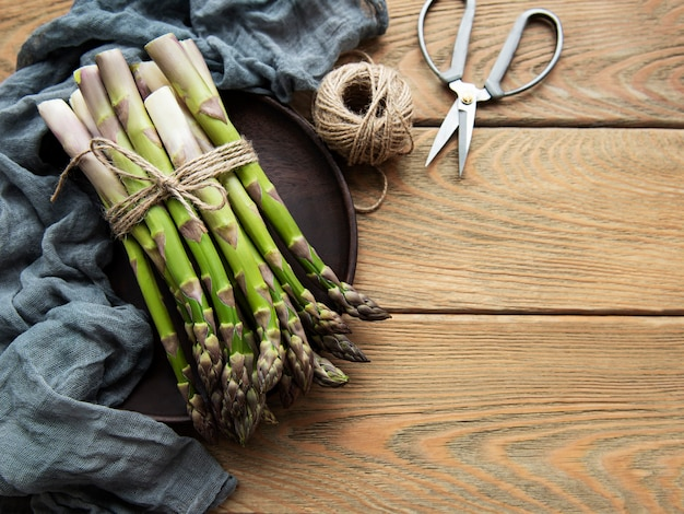 Asparagi verdi freschi con forbici e filo sulla vecchia tavola di legno