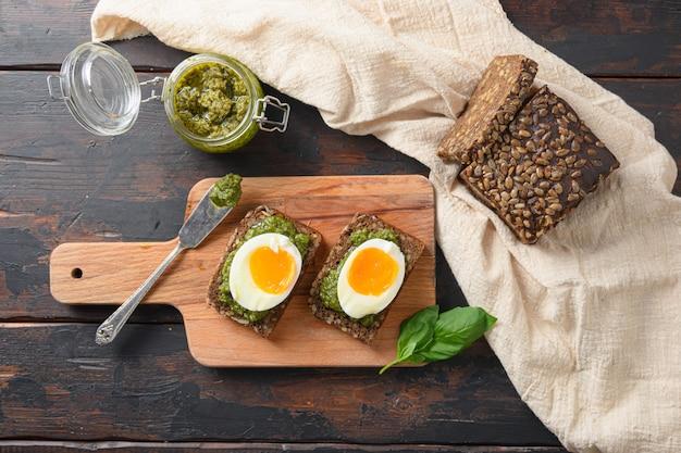 Pesto di basilico verde fresco in barattolo di vetro fatto in casa su vecchie uova di legno rustico pane panini con coltello pesto e salsa piccante sriracha colazione italiana con ingredienti pesto verde vista dall'alto