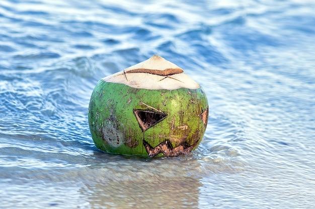 Cocco verde fresco con faccia scolpita come lanterna jack in acqua sulla spiaggia simbolo tropicale di halloween