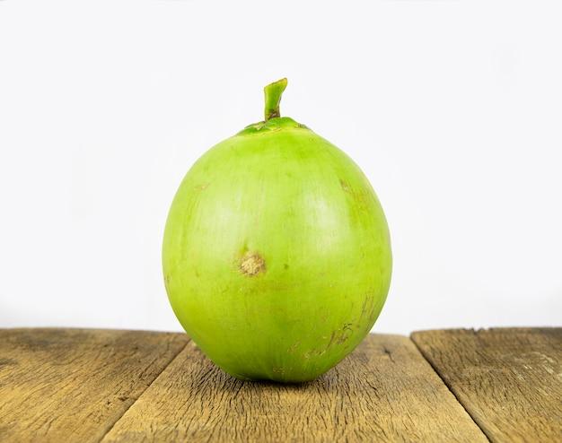 Noce di cocco verde fresca sul fondo della tavola in legno.
