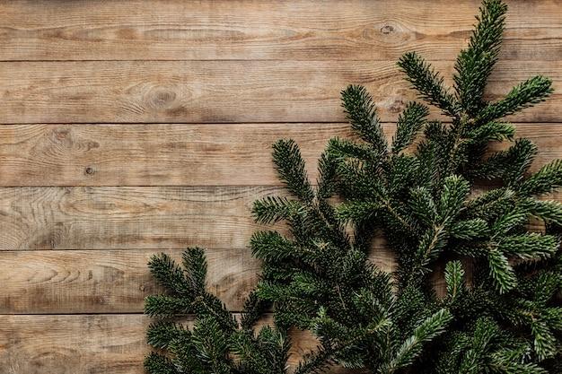 Rami di abete verde fresco su uno sfondo di legno con spazio libero per il testo.