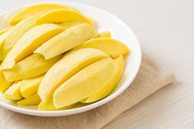 Mango verde e dorato fresco affettato sulla zolla