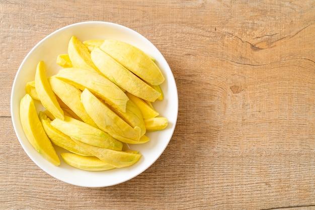 Mango verde e dorato fresco affettato sulla piastra