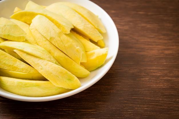 Mango fresco verde e dorato affettato sul piatto