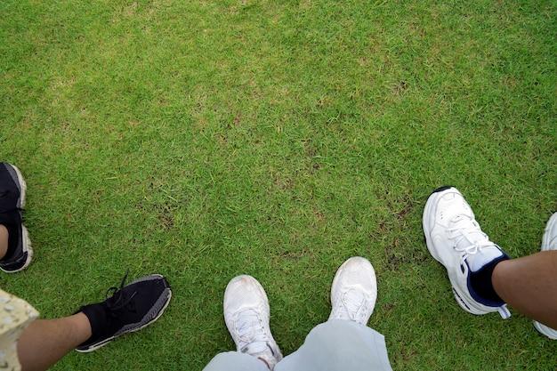 Campo di erba verde fresca con piedi su scarpe da ginnastica al confine inferiore, concetto insieme