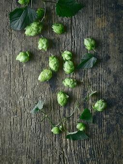 Coni verdi freschi della pianta di luppolo sul vecchio fondo di legno del tavolo da cucina, vista superiore