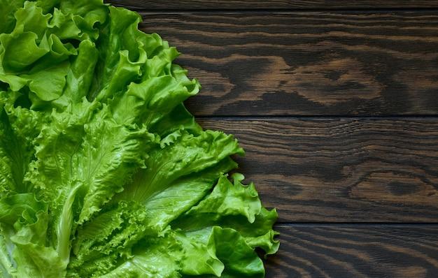 Lattuga verde fresca su fondo di legno scuro con lo spazio della copia
