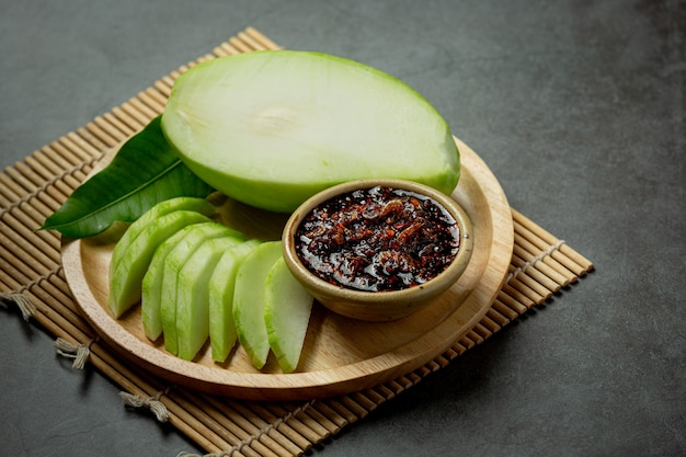 Mango verde fresco con salsa di pesce dolce immerso sulla superficie scura
