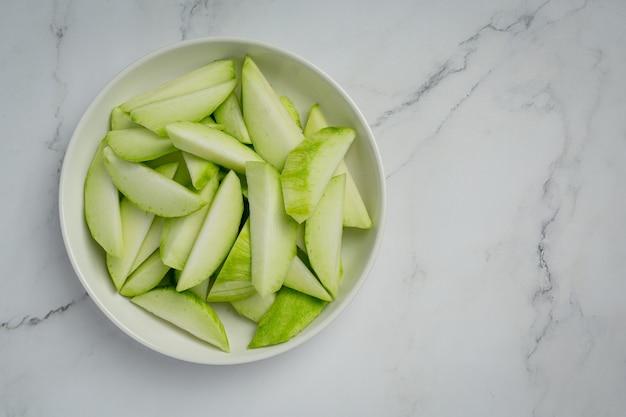 Mango verde fresco con salsa di pesce dolce immergendo sulla superficie bianca