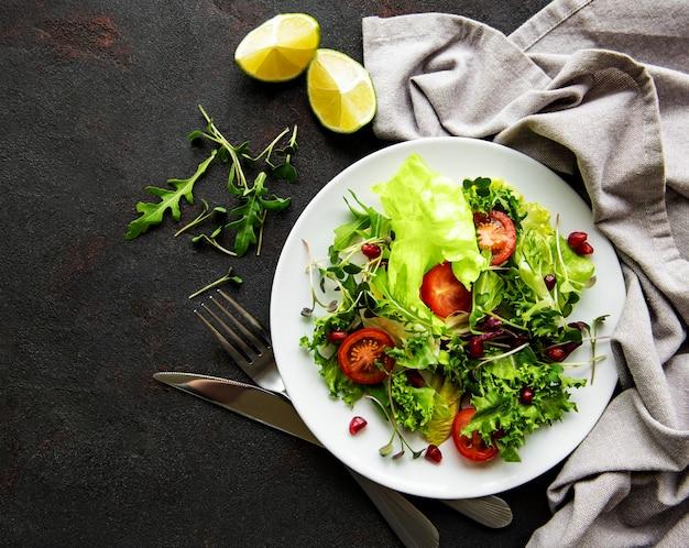 Insalatiera mista verde fresca con pomodori e microgreens su superficie di cemento nero