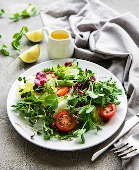 Ciotola di insalata mista verde fresca con pomodori e microgreens su una superficie di cemento