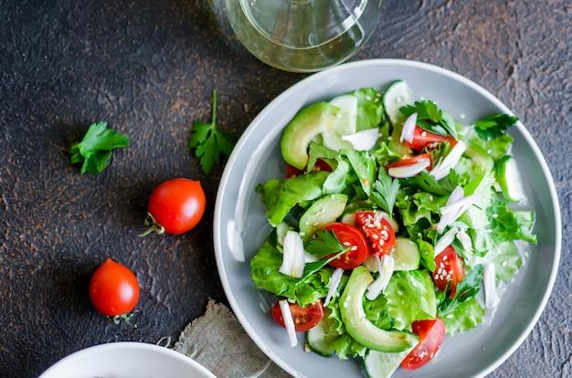 Insalata biologica verde fresca con ingredienti grezzi si chiuda. gustosa insalata con lattuga, pomodorini, cetrioli, verdure e cipolle su lastra grigia per pranzo, vista dall'alto. mangiare sano, concetto di dieta