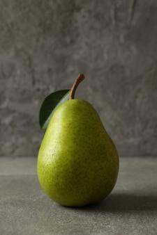 Pera verde fresca sulla tavola grigia, fine su