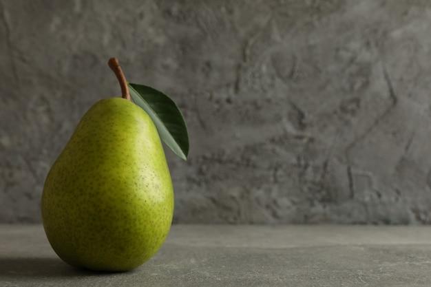 Pera verde fresca sulla tavola grigia, spazio per testo