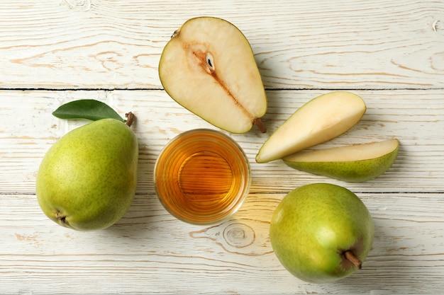 Pere e succo verdi freschi su legno