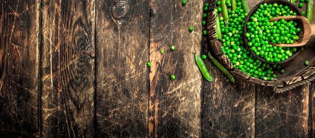 Piselli freschi in una ciotola. su uno sfondo di legno.
