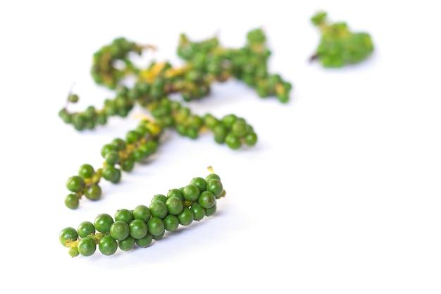 I grani di pepe verde fresco su sfondo bianco