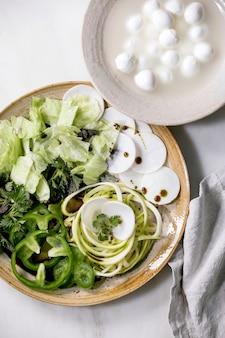 Verdure crude fresche ed erbe aromatiche spaghetti zucchine, ravanello bianco, paprika verde, insalata di ghiaccio, palline di mozzarella per cucinare l'insalata della cena. piatto in ceramica sul tavolo in marmo bianco. lay piatto