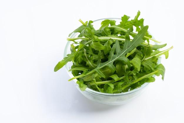 Insalata di rucola verde fresca su priorità bassa bianca.