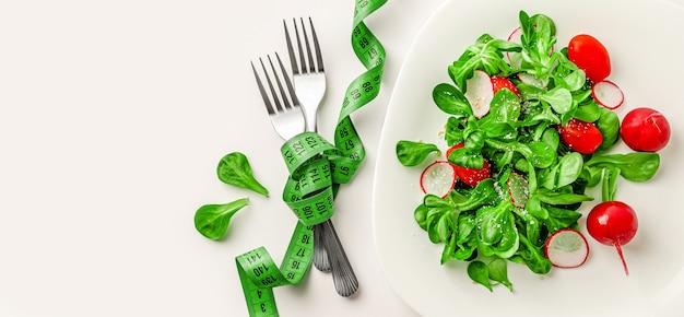 Insalata verde fresca, forchette con nastro adesivo di misurazione. copia spazio.